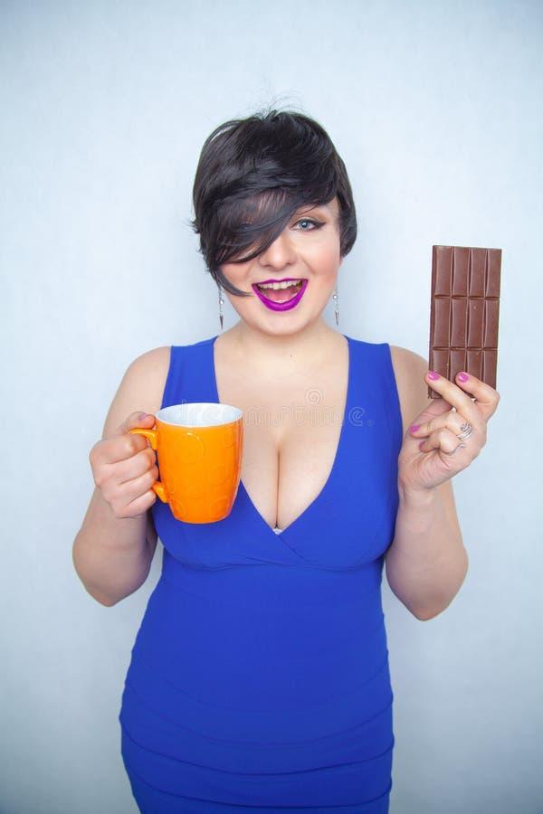 Muchacha rechoncha linda con el pelo negro corto en un vestido azul que sostiene una barra de chocolate y una taza en sus manos,  fotografía de archivo libre de regalías