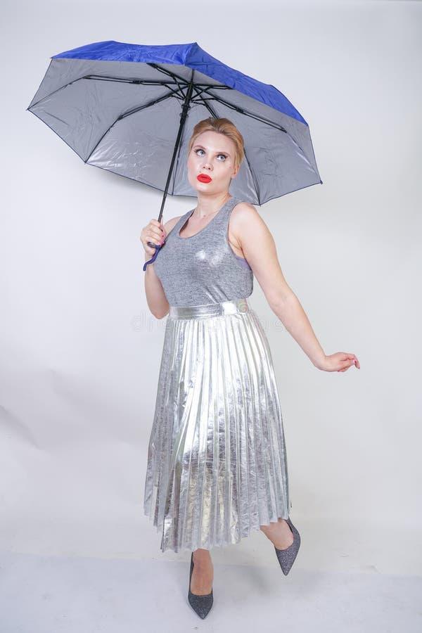 Muchacha rechoncha linda del pelo corto en un vestido moderno de la plata metalizada de la ciudad que sostiene un paraguas y que  fotos de archivo libres de regalías