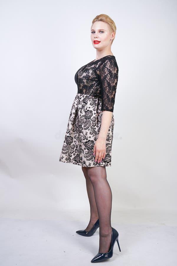 Muchacha rechoncha linda en el vestido moderno corto de la ciudad hecho de la tela blanca y del cordón negro que presentan en med fotos de archivo libres de regalías