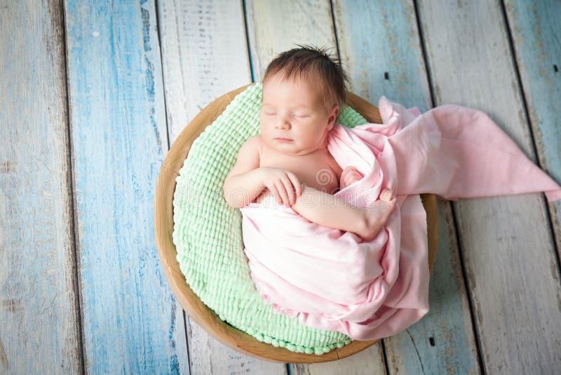 Muchacha recién nacida hermosa que duerme en una cesta fotografía de archivo