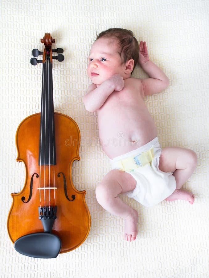 Muchacha recién nacida minúscula que miente al lado de un violín fotografía de archivo
