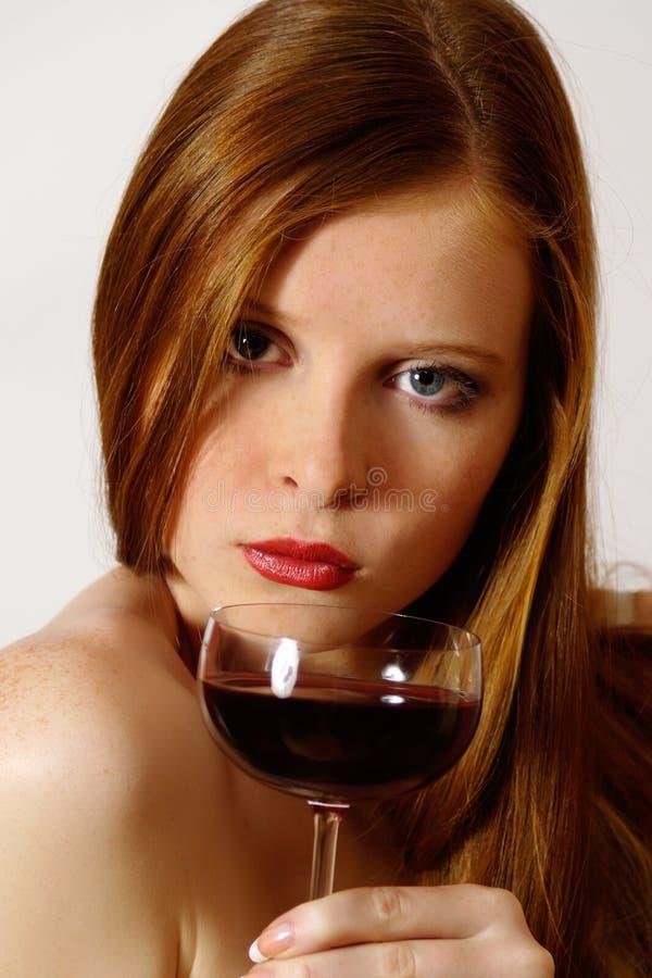 Muchacha Redheaded con el vino rojo de cristal foto de archivo