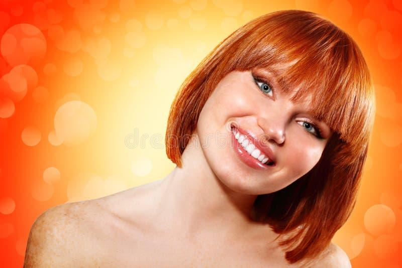 Muchacha redheaded hermosa joven sobre fondo anaranjado fotos de archivo