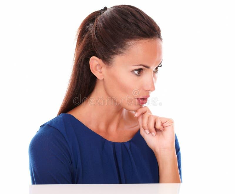 Muchacha reflexiva que mira abajo con la mano en la barbilla foto de archivo libre de regalías