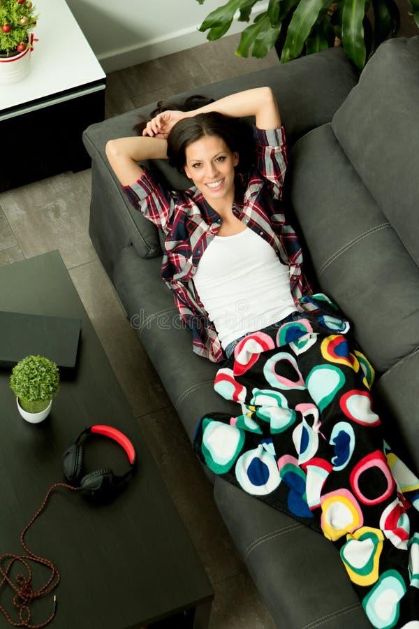 Muchacha relajada que descansa sobre el sofá en casa imágenes de archivo libres de regalías