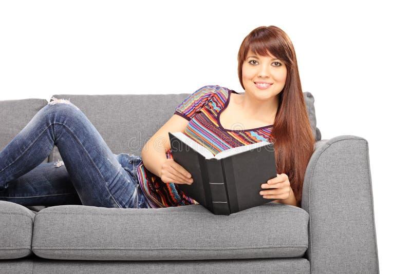 Muchacha relajada que miente en el sofá y que sostiene un libro imagenes de archivo