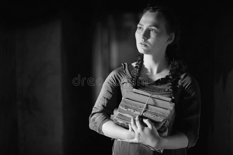 Muchacha retra en los libros de lectura viejos de la casa imagenes de archivo