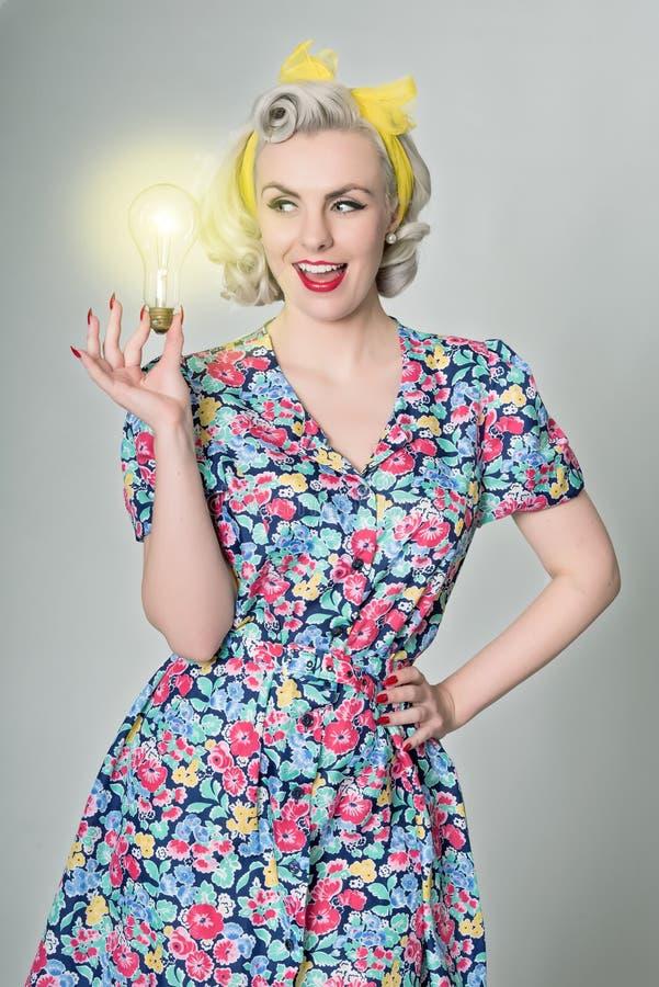 Muchacha retra rubia linda que sostiene la bombilla que brilla intensamente - concepto chistoso imagen de archivo libre de regalías