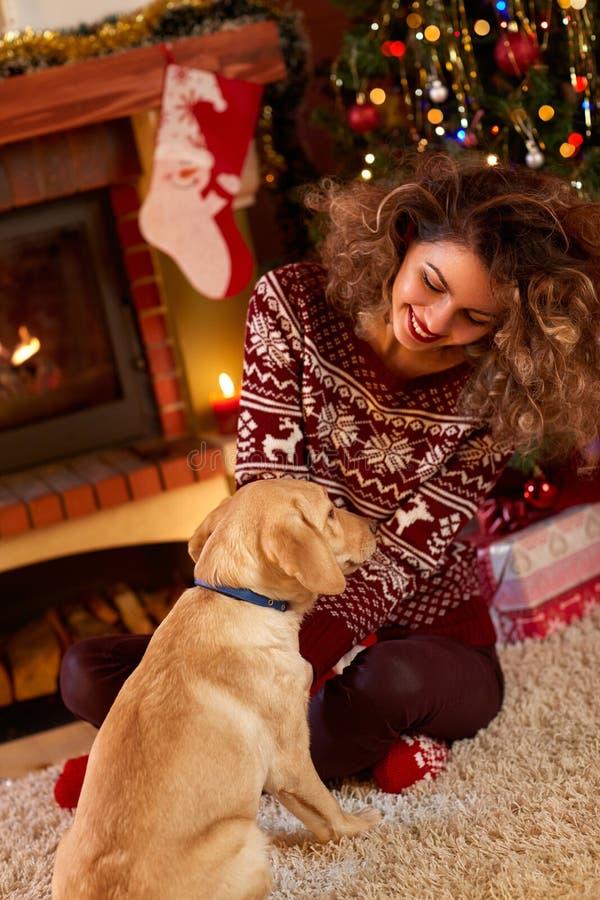 Muchacha rizada con el perro agradable por la tarde de la Navidad fotos de archivo