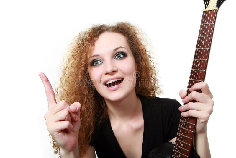 Muchacha rizada del Redhead con una guitarra foto de archivo