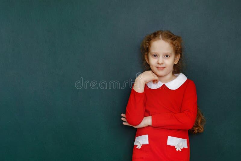Muchacha rizada elegante cerca de la pizarra verde en sala de clase Educación C imagen de archivo