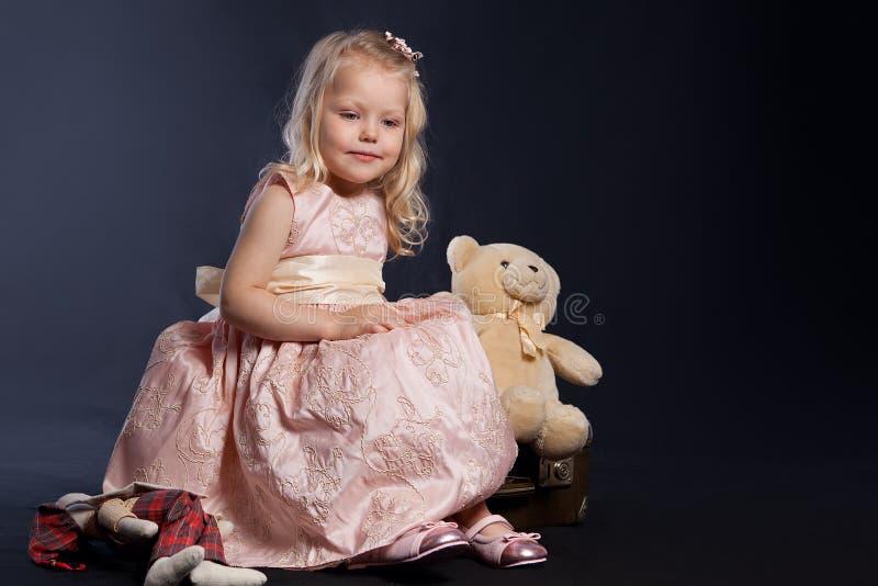 Muchacha rizada en la alineada rosada que se sienta en la maleta vieja imagen de archivo libre de regalías