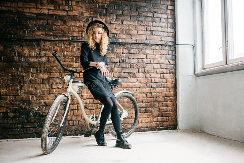 Muchacha rizada hermosa en un capo con una bici imagenes de archivo