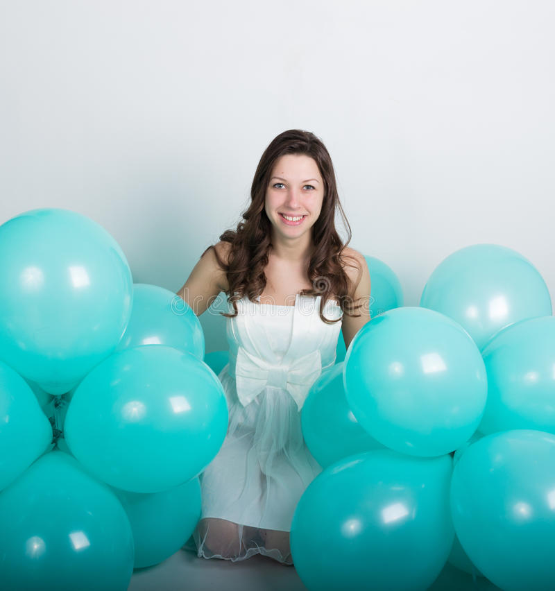 Muchacha rizada hermosa en un vestido blanco y gafas de sol en el estilo del disco que juega con los globos fotos de archivo