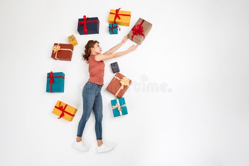 Muchacha rizada hermosa joven que miente en piso entre tiro de las cajas de regalo desde arriba de aislado imágenes de archivo libres de regalías