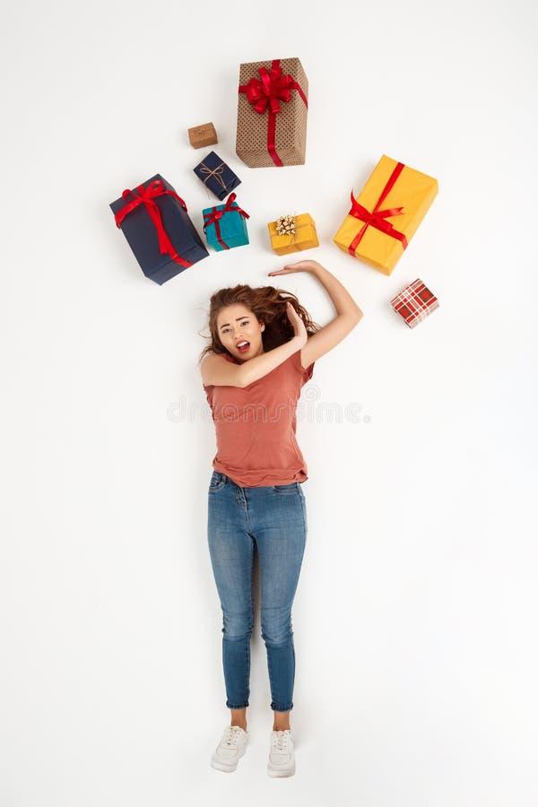 Muchacha rizada hermosa joven que miente entre tiro de las cajas de regalo desde arriba de aislado imagen de archivo libre de regalías