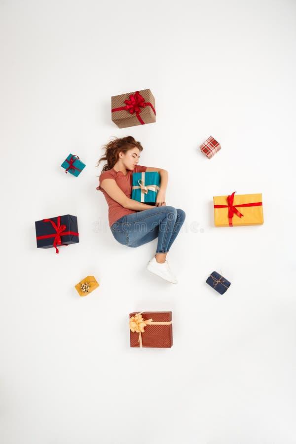 Muchacha rizada hermosa joven que miente entre tiro de las cajas de regalo desde arriba de aislado foto de archivo libre de regalías
