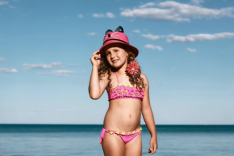 Muchacha rizada joven en un traje de baño rosado que se relaja en la playa en el sombrero, el Mar Negro, Odessa, Ucrania, lugar p imagen de archivo