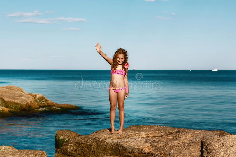 Muchacha rizada joven en un traje de baño rosado que se relaja en las rocas en la playa, el Mar Negro, Odessa, Ucrania, un lugar  fotografía de archivo