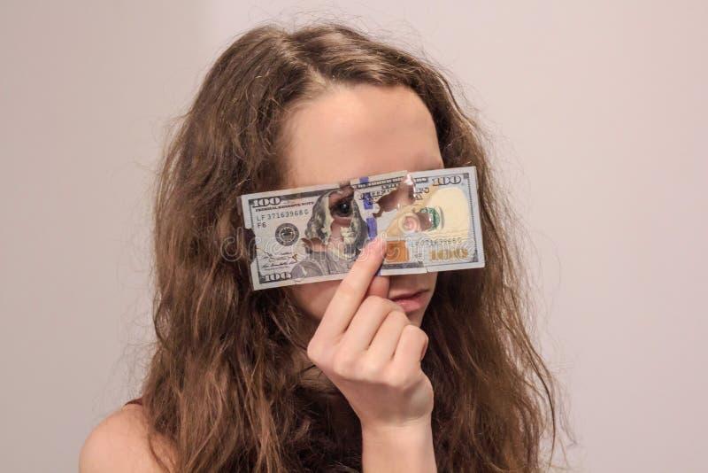 Muchacha rizada que mira sin embargo el billete de banco del dólar imágenes de archivo libres de regalías