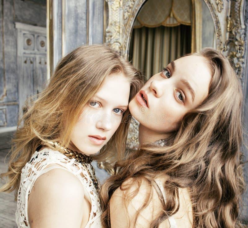 Muchacha rizada rubia del peinado de la hermana bastante gemela dos en interior de lujo de la casa junto, primer rico del concept fotografía de archivo libre de regalías
