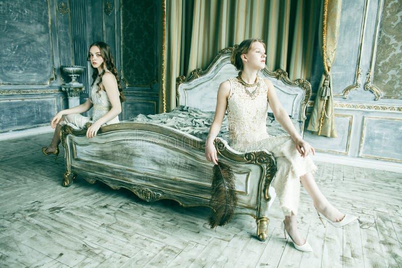 Muchacha rizada rubia del peinado de la hermana bastante gemela dos en interior de lujo de la casa junto, concepto rico de la gen foto de archivo libre de regalías
