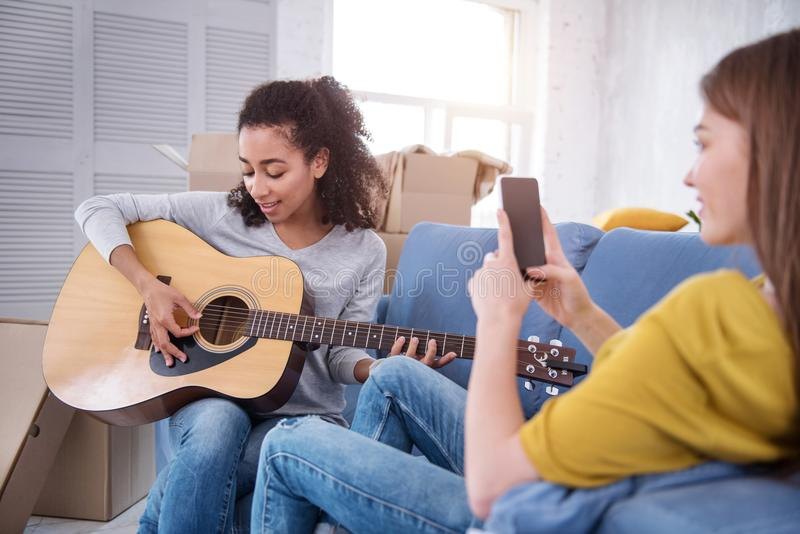 Muchacha rizado-cabelluda encantadora que toca la guitarra para el compañero de cuarto foto de archivo libre de regalías