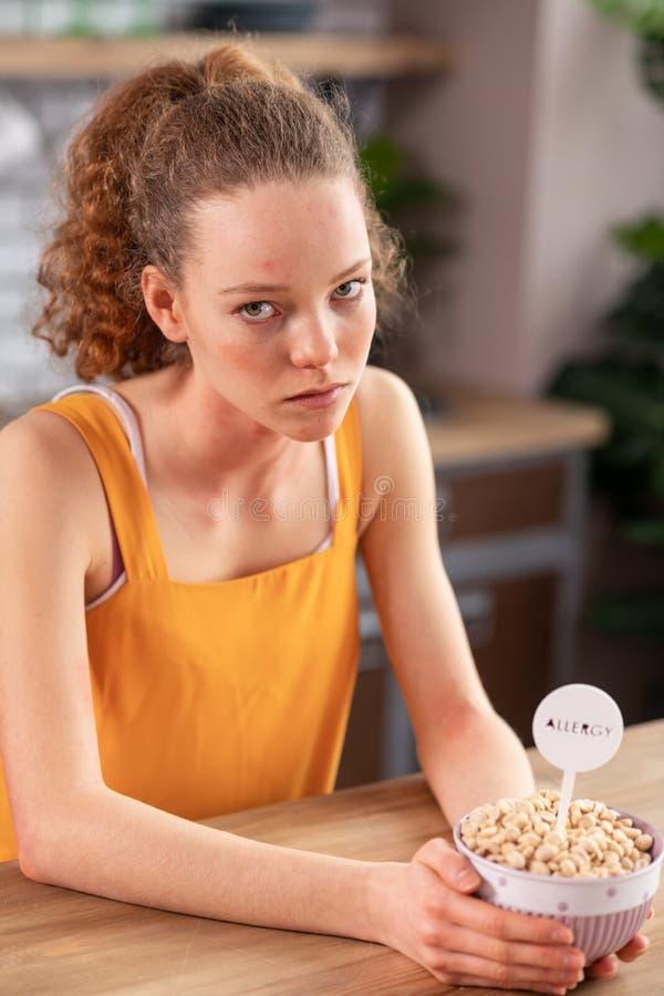 Muchacha rizado-cabelluda infeliz que está contrariedad con la comida en cuenco imagen de archivo