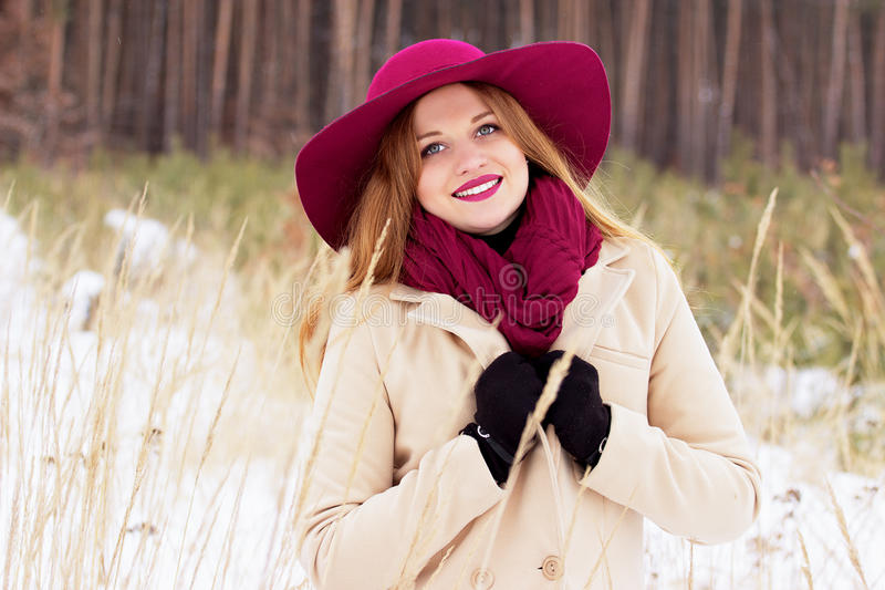 Muchacha roja joven, hermosa y elegante de la sonrisa del pelo en capa y sombrero en la moda del bosque fotografía de archivo libre de regalías