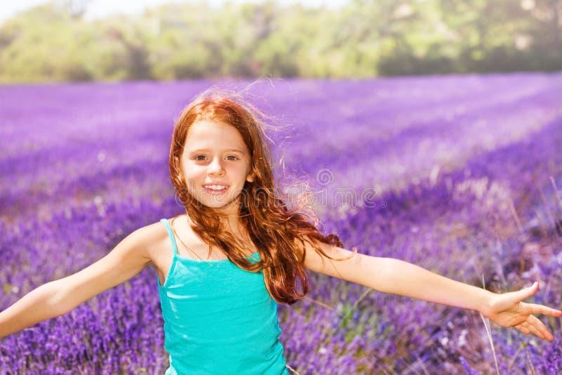 Muchacha rojo-dirigida feliz que se divierte en campo de la lavanda fotos de archivo