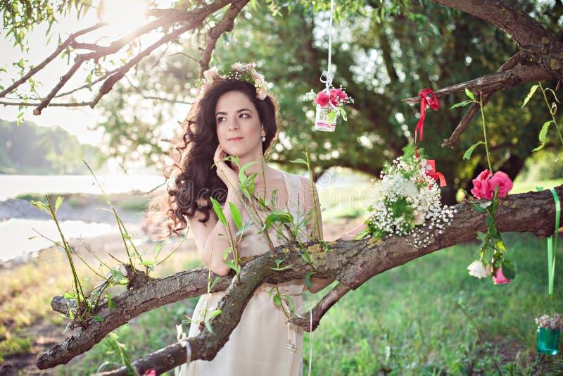 Muchacha romántica del boho joven hermoso con la guirnalda de la flor imagen de archivo
