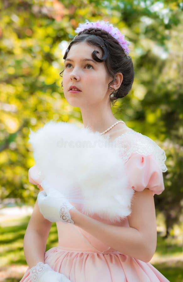 Muchacha romántica, encantadora que se aviva fan y con un attentiv foto de archivo libre de regalías