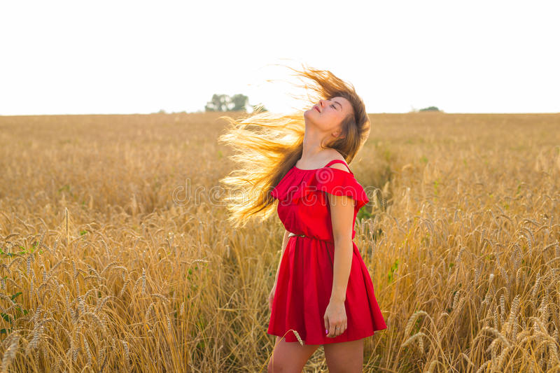 Muchacha romántica magnífica al aire libre Modelo hermoso en vestido rojo corto en campo Pelo largo que sopla en el viento Retroi fotografía de archivo