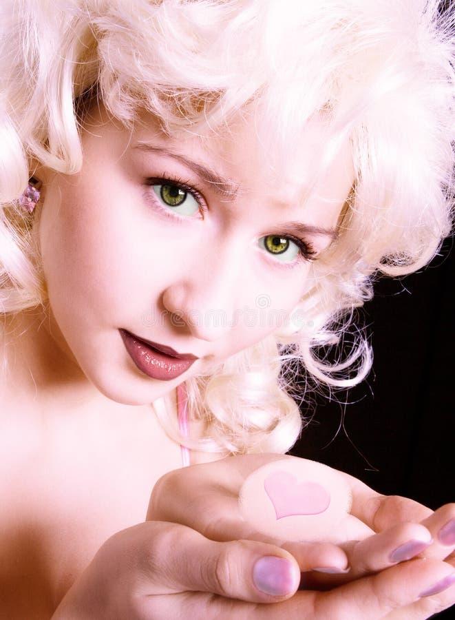 Muchacha rosada de la belleza con el corazón en hend foto de archivo
