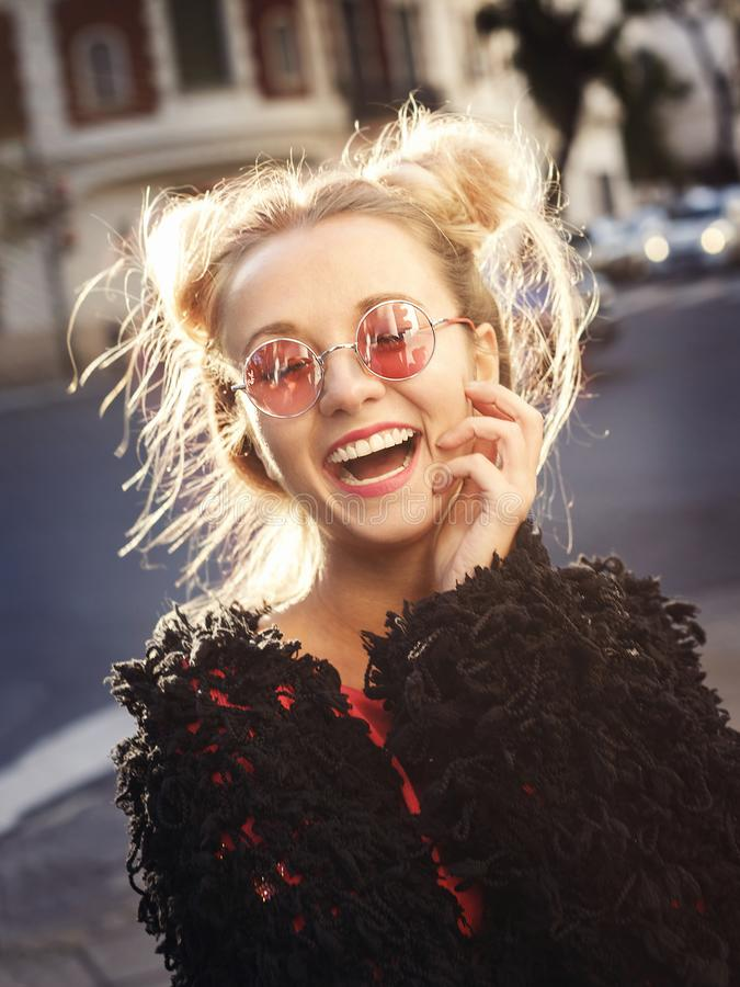 Muchacha rubia alegre en vidrios color de rosa que se ríe ruidosamente imagen de archivo libre de regalías