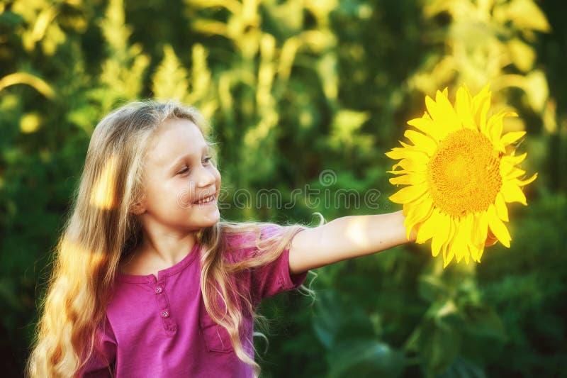 Muchacha rubia alegre que sostiene una flor del girasol en sus manos foto de archivo libre de regalías