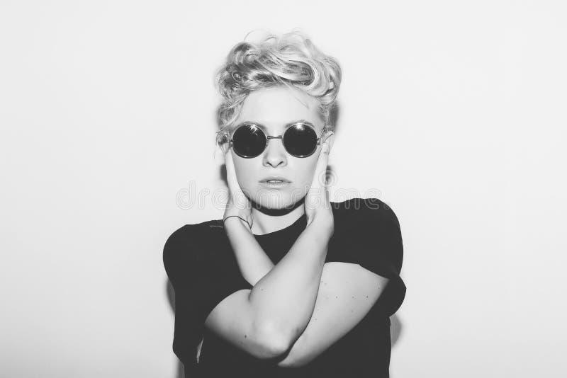 Muchacha rubia atractiva de la moda elegante mala en una camiseta negra y gafas de sol de la roca Mujer emocional rocosa peligros foto de archivo libre de regalías