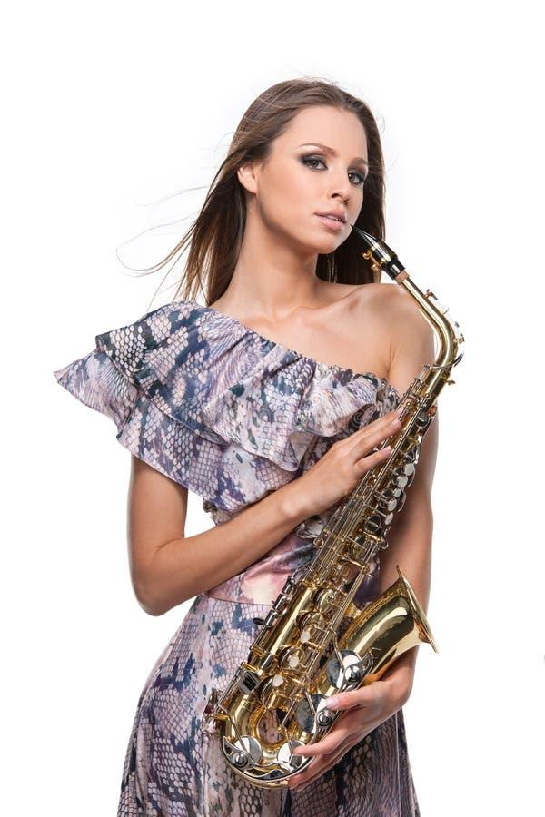 Muchacha rubia atractiva que presenta con el saxofón. fotografía de archivo
