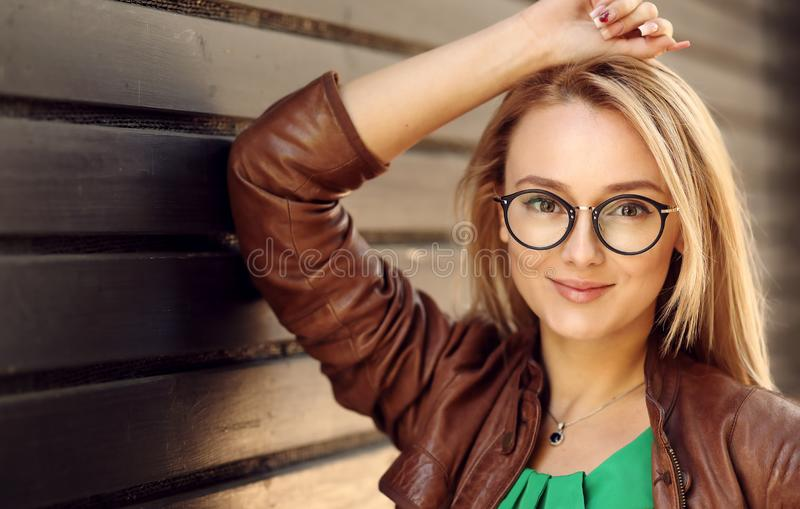 Muchacha rubia atractiva sonriente con el maquillaje natural de la cara que lleva los vidrios ópticos del ojo de la moda elegante imagen de archivo libre de regalías