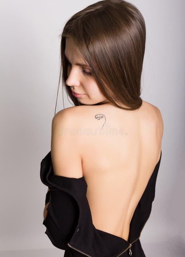 Muchacha rubia atractiva trasera del primer, ella saca su vestido la inscripción en el hombro goza fotografía de archivo libre de regalías