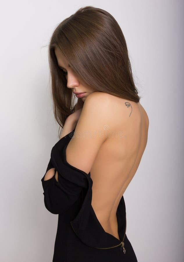 Muchacha rubia atractiva trasera del primer, ella saca su vestido la inscripción en el hombro goza imagen de archivo