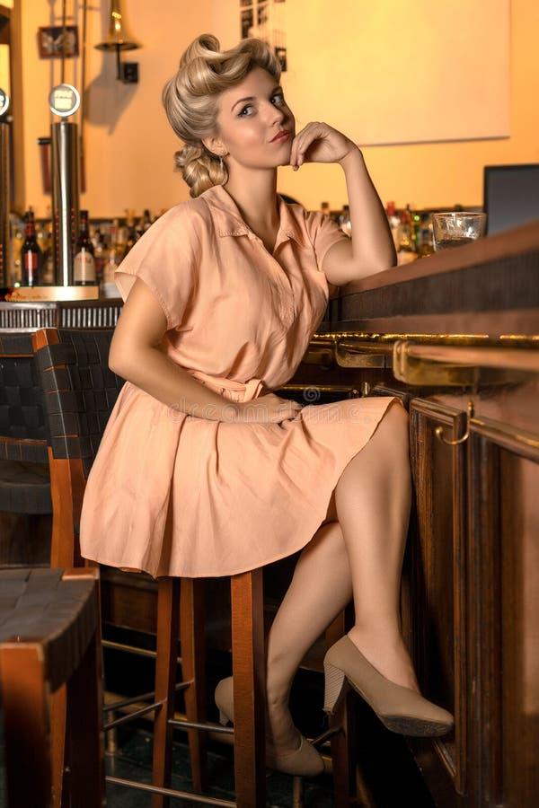 Muchacha rubia bonita en el estilo de los años 50 que esperan sentarse e inclinarse en un contador de la barra imagen de archivo