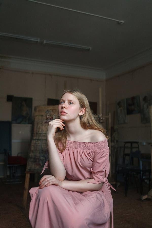 Muchacha rubia bonita joven en el vestido rosado que apoya su cabeza con el brazo en el estudio del arte, mirando cuidadosamente  fotografía de archivo