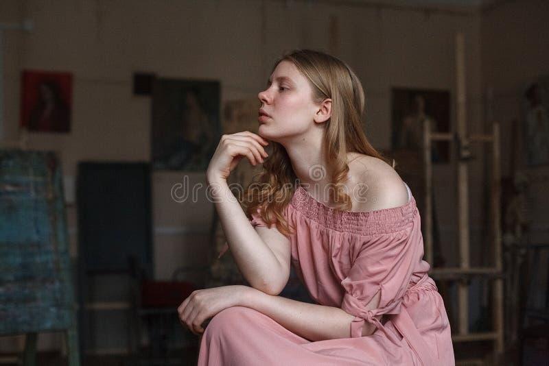 Muchacha rubia bonita joven en el vestido rosado que apoya su cabeza con el brazo en el estudio del arte, mirando cuidadosamente  imagenes de archivo