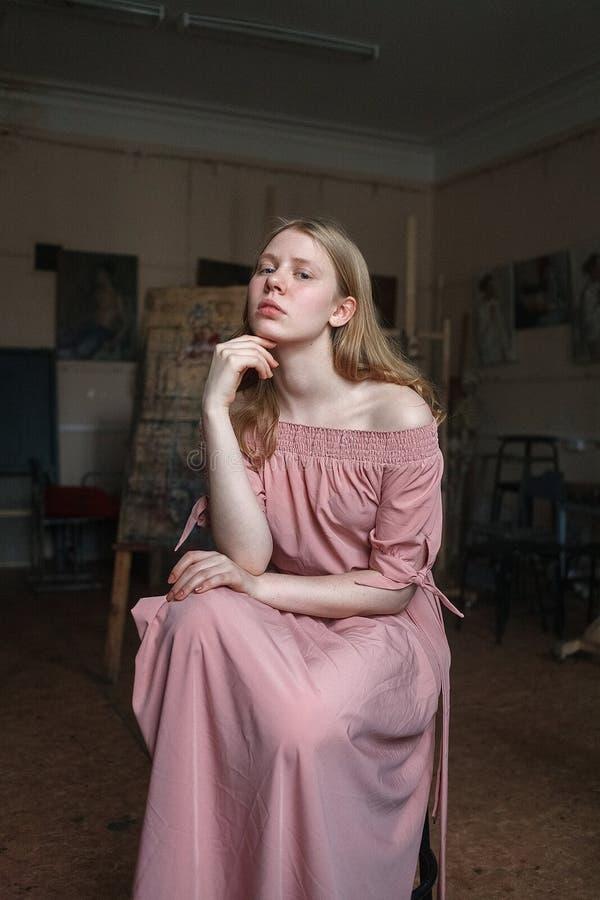 Muchacha rubia bonita joven en el vestido rosado que apoya su cabeza con el brazo en el estudio del arte, mirando questioningly e foto de archivo