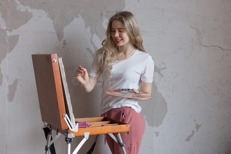 Muchacha rubia bonita sonriente joven con la situación del cepillo y de la paleta cerca de la imagen del dibujo del caballete Ar fotografía de archivo