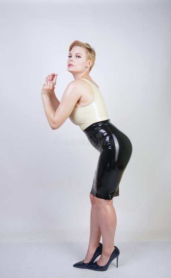 Muchacha rubia caliente del pelo corto con el vestido de goma del l?tex del cuerpo que lleva con curvas en el fondo blanco del es imagen de archivo