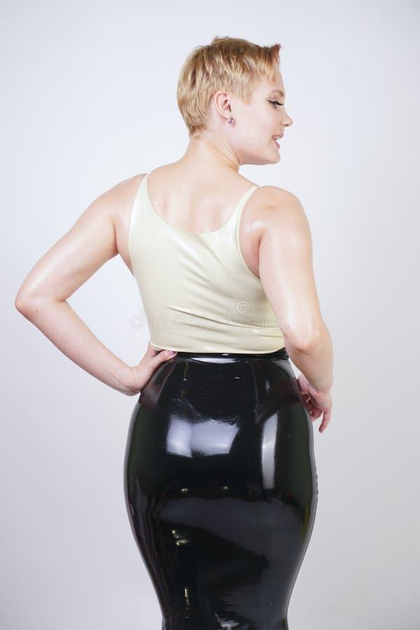 Muchacha rubia caliente del pelo corto con el vestido de goma del l?tex del cuerpo que lleva con curvas en el fondo blanco del es imagen de archivo libre de regalías