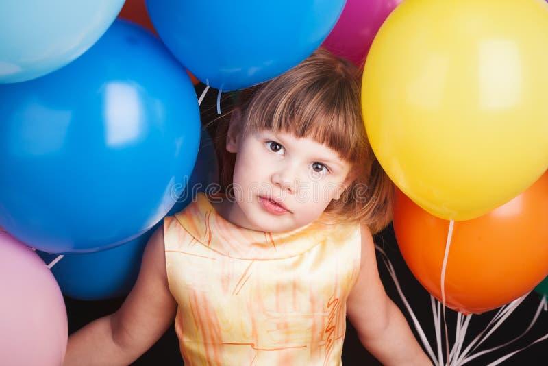 Muchacha rubia caucásica con los globos coloridos fotografía de archivo libre de regalías