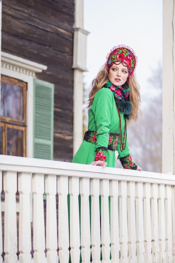 Muchacha rubia caucásica en vestido verde de moda y Kokoshnik con el modelo florido y las gotas Presentación contra casa de mader imagenes de archivo